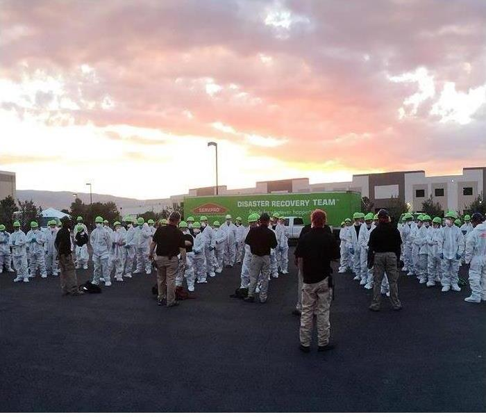 SERVPRO Commercial Large Loss Team Lined up in white hazmat suites and SERVPRO Uniforms
